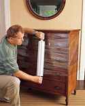 Wrap Furniture When transporting anything with doors or drawers, such as bureaus, cabinets, or large appliances, wind a few layers of plastic wrap around the item to secure it. This eliminates the need for tape, which can damage delicate surfaces, and helps safeguard against scratches. Plastic wrap can also protect upholstered furniture against dirt.