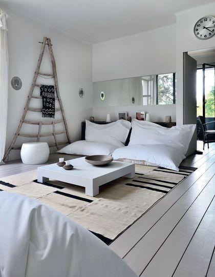 On adore la déco zen de ce salon : gros coussins en guise de canapé, table basse en bois laqué et pouf rond en résine