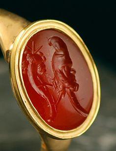 Le chaton ovale est orné d'une intaille romaine gravée sur une cornaline rouge orangée, de surface légèrement bombée, d'un sujet exceptionnel représentant un grylle en forme de perroquet portant une tête de Silène en guise de dos. Il tient entre ses pattes la corne d'abondance. Sujet inconnu à ce jour ! Très bon état, belle gravure nette et profonde.Monture moderne en or massif 22K de style néo-classique, à fond clos.Intaille d'époque romaine, probablement du 1er siècle avant – 1er siècle…