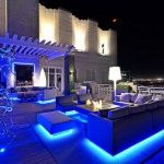Blue Colored Neon Lighting in A Hardwood Deck With Shade And Fireplace