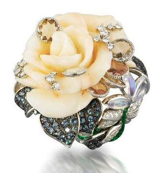 """An enamel, coral and gem-set rose ring, by Dior The carved coral rose scattered with brilliant-cut diamond and circular-cut quartz """"droplets"""", encircled by pavé-set tourmaline leaves, on a green glitter enamelled hoop modelled as a winding stem with pavé-set diamond and navette-shaped cabochon moonstone leaf spray terminal, signed Dior and numbered, French maker's mark and assay mark."""