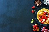 Thin pancakes with strawberries, grapes, dragon fruit, golden kiwi and honey over black background with a copy space.