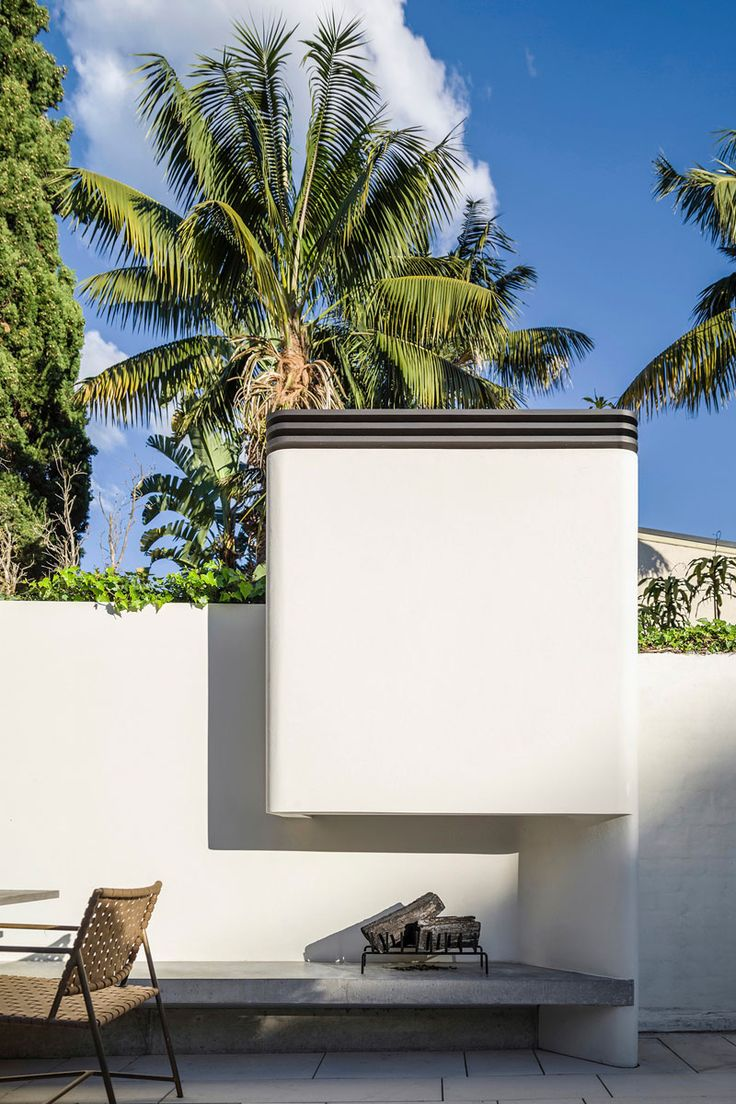 This modern courtyard has a built-in fireplace that sits at the end of a built-in concrete bench.