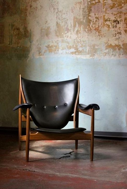 chair designed by Finn Juhl set against worn concrete floor and wall