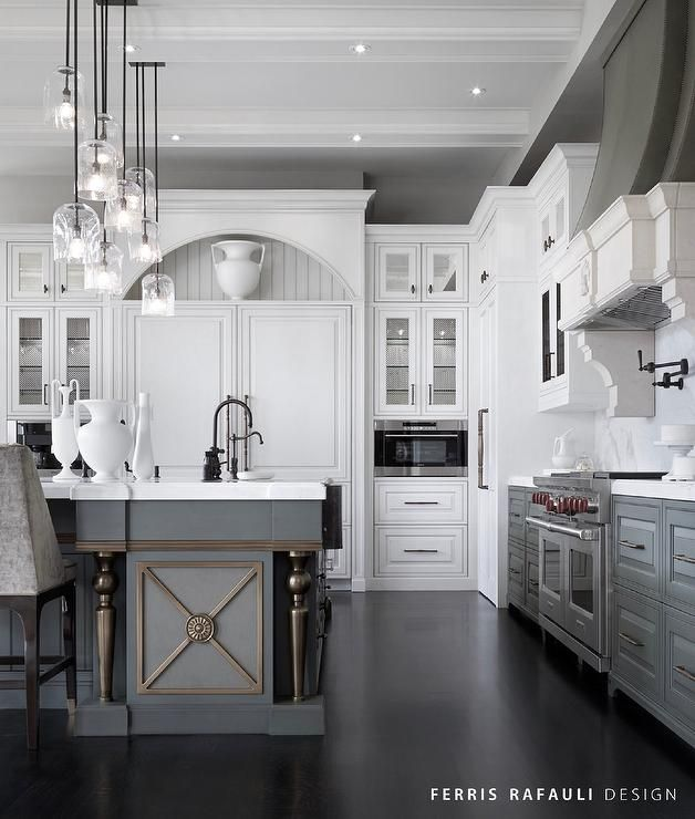 White and gray kitchen features white upper cabinets and gray lower  cabinets paired with honed white marble countertops and a white marble slab  backsplash.