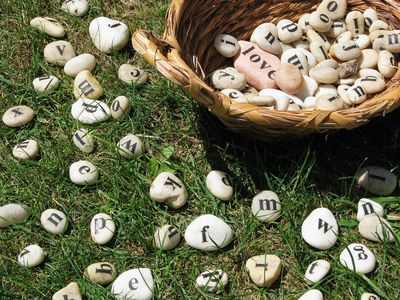 Spelling In The Grass. Use smooth stones to make a spelling game you can play on the lawn. Stamp letters onto the rocks, or use rub on transfers.    From The Write Start.