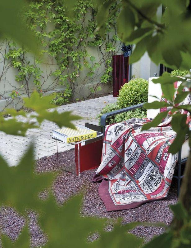 Piensa en verde La frondosidad y los aromas naturales del jardín lo convierten en un placer cotidiano. Sobre la silla de hierro, una manta de Hermès.