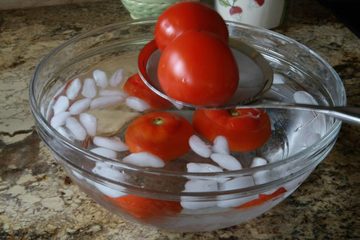 Canning Tomatoes. After boiling, plunge tomatoes in ice water to help skins slip off easily. More on canning tomatoes: http://www.tomatodirt.com/canning-tomatoes.html.
