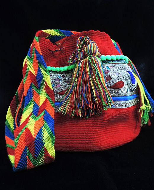 Mochila Wayuu decorada con adornos étnicos.