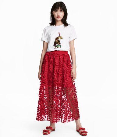 Röd. En vadlång kjol i tyll med broderier och applikationer. Kjolen har resår i midjan. Delvis fodrad.