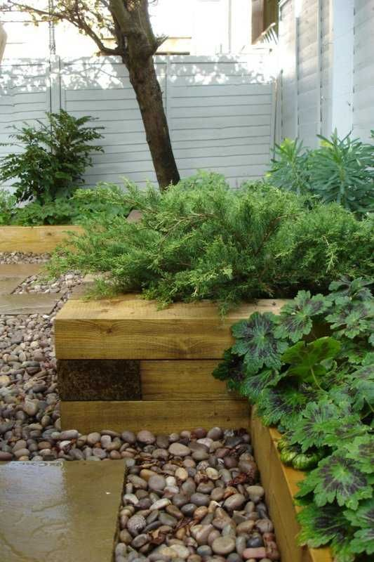 nice combo of wood, pebble and paver with shrubbery