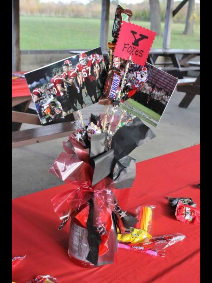Gatorade bottle turned into Homecoming centerpieces with a cut styrofoam ball on top and some skewers with pictures and candy.  Streamers cut up and wrapped with garland for some sparkle!