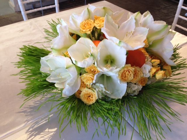 White amaryllis, oranges and spray roses in a bed of wheat grass...