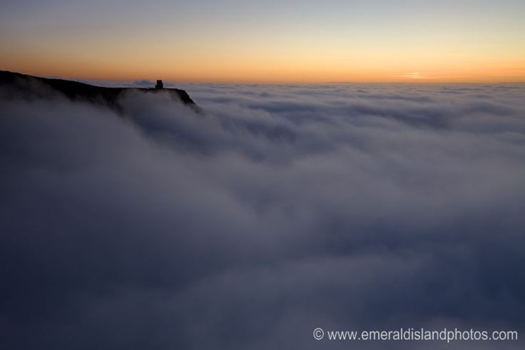 Cliffs of Moher and O'Brien's tower in the foggy sunset, County Clare, Ireland.