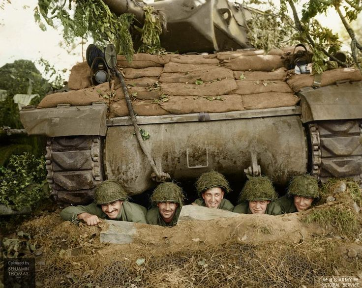 A US tank crew posing for the camera from a foxhole beneath their M-10 tank destroyer, north of Marigny, Normandy, 26 July 1944. The men belong to the 703rd Tank Destroyer Battalion attached to Combat Command B of the 3rd Armored Division. The unit landed in France on 1 July, & saw its first action near Hautes Vents a fortnight later. This photo was taken in the intervening week, before the unit participated in Operation Cobra.