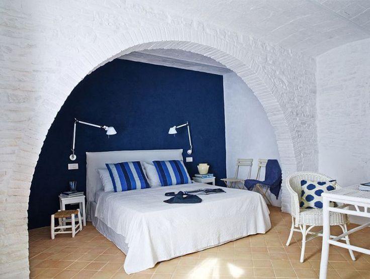 В спальне первого этажа настроение создается успокаивающим синим цветом. Уюта добавляет мебель из ротанга.  (средиземноморский,средиземноморский интерьер,средиземноморский дом,средиземноморский стиль,деревенский,сельский,кантри,архитектура,дизайн,экстерьер,интерьер,дизайн интерьера,мебель,спальня,дизайн спальни,интерьер спальни) .