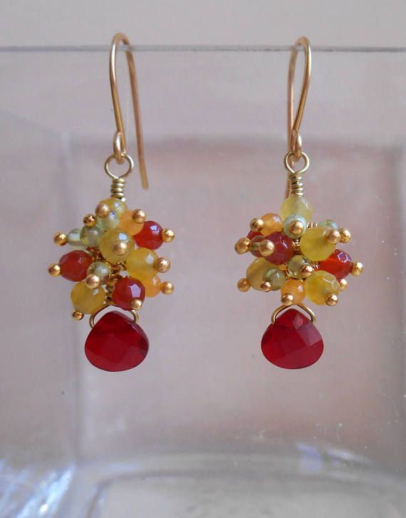 With their playful composition and bold, vibrant color story, these petite gemstone cluster earrings are comfortable, sophisticated and versatile. A wine red hand cut pear faceted briolettes is adorned by a rich cluster of colourful gemstones: orange red faceted carnelian beads,