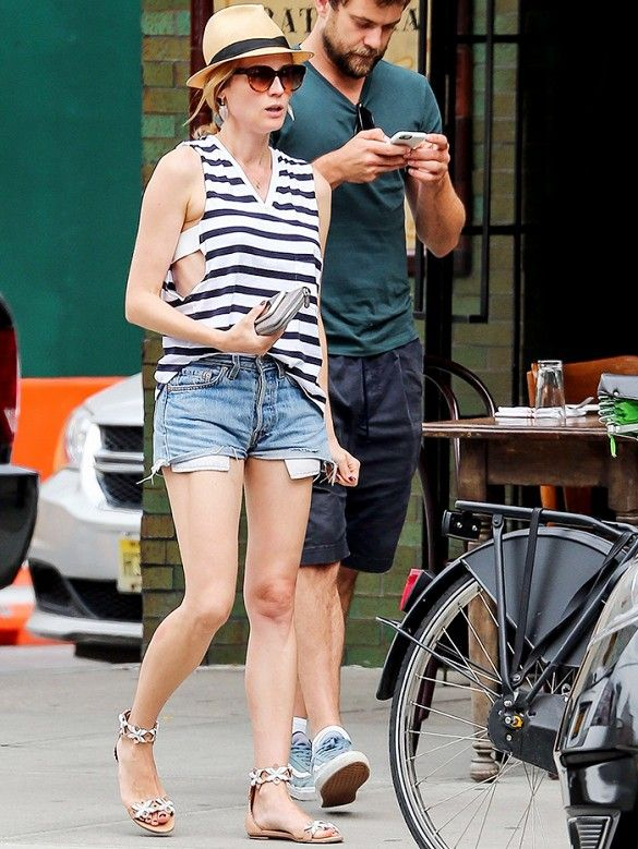 Diane Kruger wears a striped tank top, denim cutoffs, ankle-strap sandals, and a fedora