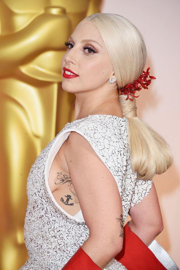 Lady Gaga con recogido bajo y tocado del mismo color de los guantes.