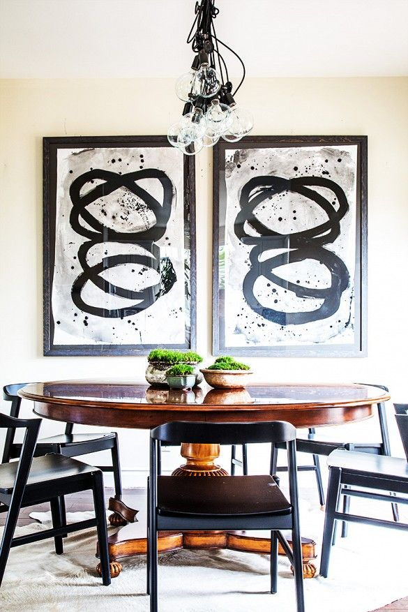 Dining area with round table, exposed bulb chandelier, and large artwork.