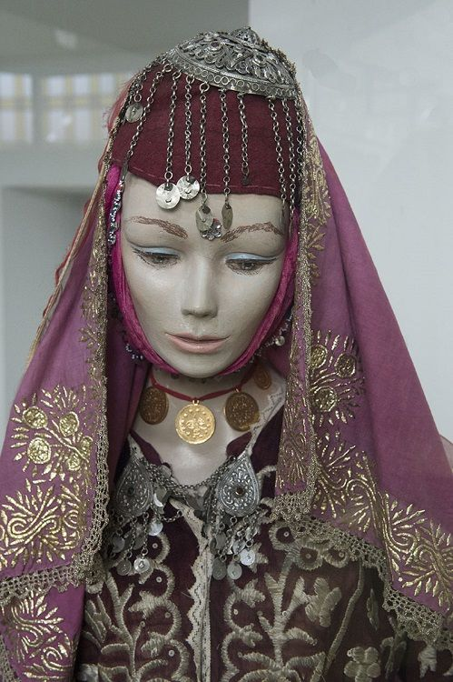 Close-up of a traditional urban bride.  Late-Ottoman, from Bursa. Ca; 1900.  The metal ornament fixed on top of the felt hat is called 'tepelik'.  On the breast: a small fastener-like ornament, consisting of two small silver(y) plaques (with dangles, and one hook each on the backside) connected with each other by three short chains.  On exhibit in the Bursa  Etnografya Müzesi.  (© Dick Osseman).