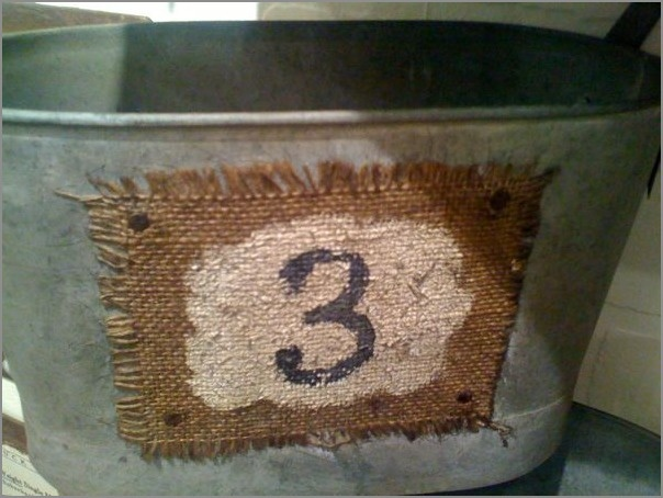 "Metal Tub...with piece of burlap, painted & stamped with number ""3"", and attached to the container."
