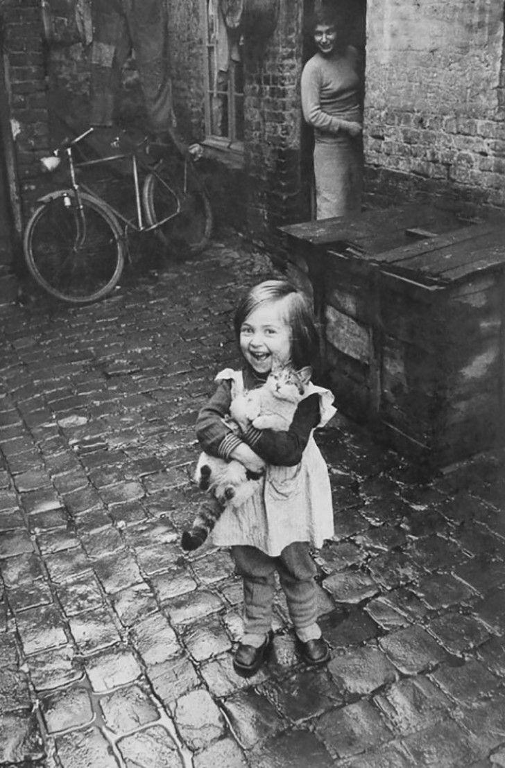 het plezier van dit Franse meisje dat haar gelukskatje op de arm heeft (1959)