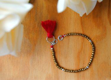 Bracelet with golden seed beads, tibetan silver beads, red tassel #gioielì #bracelet #tassel #seedbeads #tibetansilver
