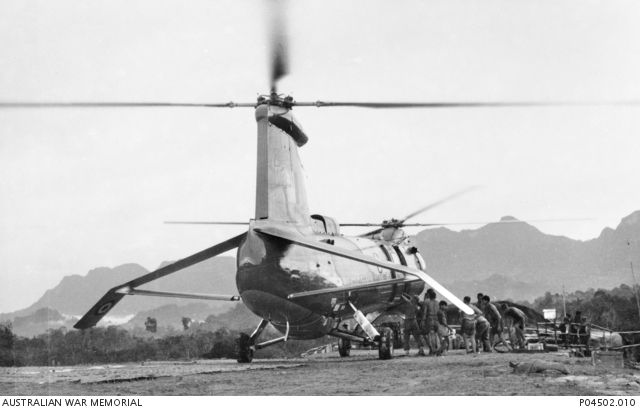 Rear view of a Belvedere heavy lift transport helicopter from 66 Squadron, RAF, on the helipad at the A Company, 3rd Battalion, The Royal Australian Regiment (3RAR), forward base at Stass. The engines are still running with the rotors spinning as it is unloaded by unidentified Australians and men from a local Kampong (village).