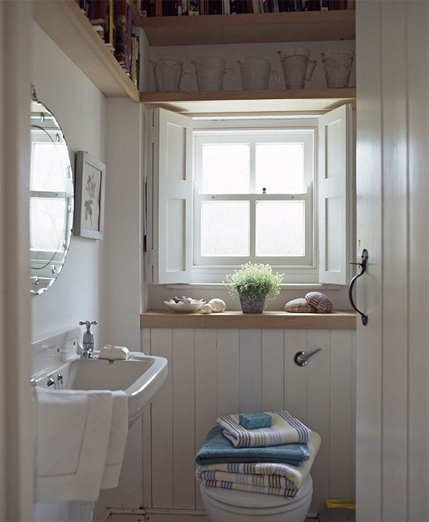 Small bathroom decorating ideas with high shelving above the window frame