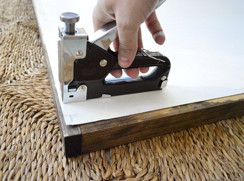 Staple a poster to the back of some wood trim pieces. Quick and easy.