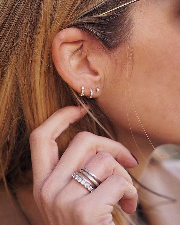 piercing oreille, manucure noire, cheveux blond cuivré avec racines brun, anneau oreilles en or