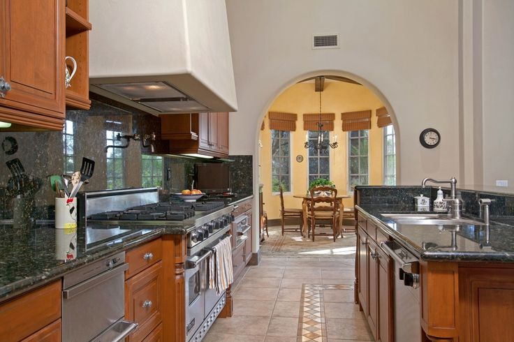 Mediterranean Kitchen with limestone tile floors, Quartz counters, Ms international emerald pearl granite, Kitchen island