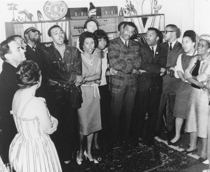 """Lorraine Hansberry during """"impromptu song-session"""" at a SNCC fundraiser at the home of actor and activist Theodore Bikel. (left to right) Avon M. Rollins, Lorraine Hansberry, Theo Bikel, Nina Simone, Marion Barry, Jr., John Lewis, unidentified man, unidentified woman, Ella Baker. July 6,1963. The Student Nonviolent Coordinating grew out of a student meeting organized by Ella Baker at Shaw University in 1960."""