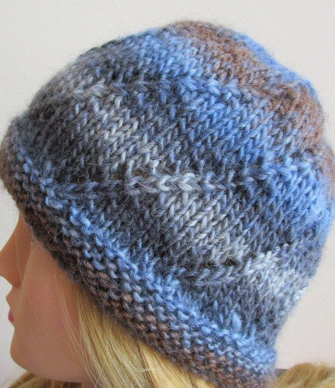 Great colour blend of denim and dirt - denim, blue, grey and brown.  This neat little hat features a lovely swirl pattern that enhances the quirky colour blend of this pure wool yarn.  Ideal for casual wear it is a warm and comfy option for chilly mornings and cool evenings.   Sized to fit an average adult - it is 7.5 inches from brim to crown and 18 inches in the round.   As this is a knit item there will be some stretch so fit should not be a problem.As with all my knits it has been hand…