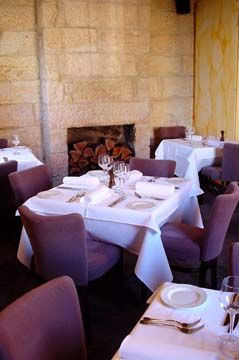 Soft furnishings in an aubergine colour contrasted to the original sandstone walls