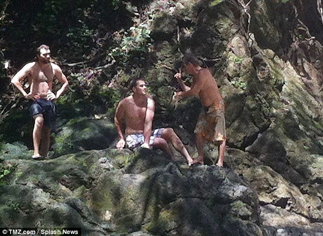 Safety in numbers: Tom Brady (in the middle) sits at the top of the cliff with two friends