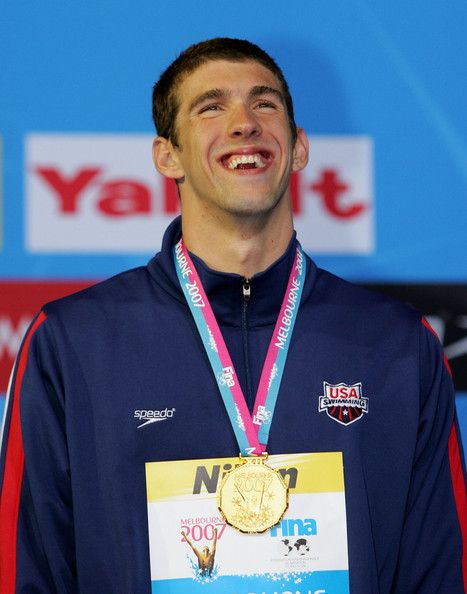 Michael Phelps Photos Photos - Michael Phelps of the USA poses with his gold medal following his win and new world record in the Men's 200m Butterfly Final during the XII FINA World Championships at the Rod Laver Arena on March 28, 2007 in Melbourne, Australia. - XII FINA World Championships - Day 12