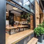 壁際に縁側的なベンチシートのある開放的なカフェのダイニング コーナーから