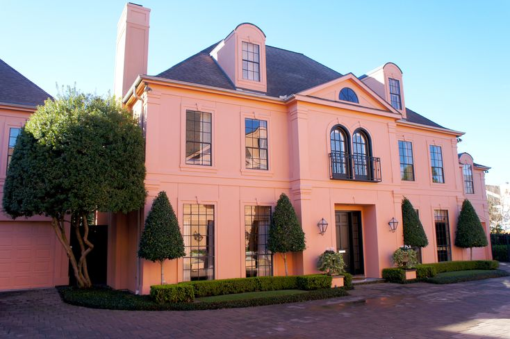 European chateau style home with french-inspired landscape design. Boasts classic finials and garden decor. Synthetic lawn bordered with red brick and accented by boxwood hedges. Outdoor seating on flagstone patio. An elegant oasis of European tranquility.