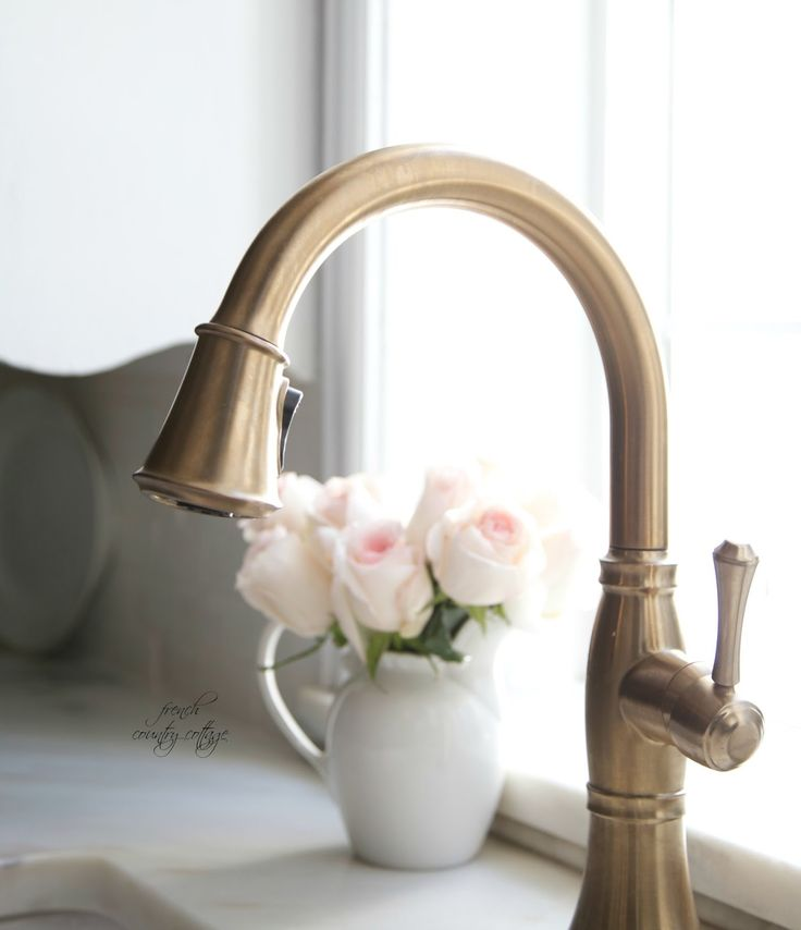 A faucet with a champagne bronze finish adds elegance to the farmhouse sink.   - CountryLiving.com
