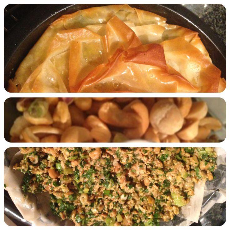 Filodeeg-notentaart ( vega / bastilla) - marokaans.  Olijfolie, 115 gr boter, 8 lente-uitjes, 2 tegen knoflook (fijn), 25 gr gember (fijn), 225 gr ongezouten noten ( cashew, pistache en macadamia) grof gehakt, 2 tl kaneel, ½ tl cayennepeper, 1 tl paprikapoeder, ½ tl korianderpoeder, zout en peper, 6 eieren losgeklopt, 35 gr platte peterselie fijn, 25 gr verse koriander fijn, 8 vellen filodeeg.   Bakvorm van 25 cm ø  Deze taart was een van de toppers tijdens een posters-buffet. De…