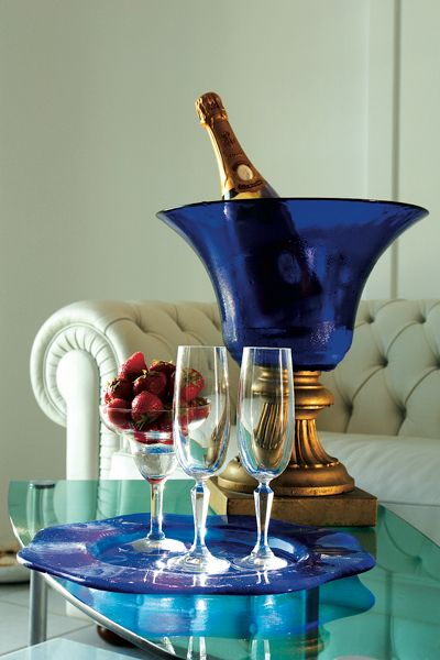 Dark blue tulip shaped bowl keeps champagne cold resting on top of a gold column pedestal. Makes for an elegant set up along with the matching glass plate.