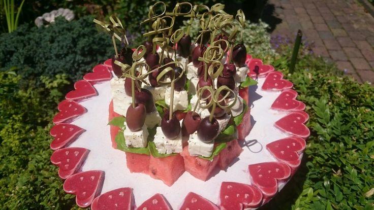 Olijf/feta/basilicum/watermeloen stokje op zelfgemaakt keramieken bord.