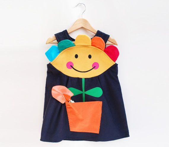 Little girls and baby pinafore dress in navy cord with a applique smiley flower face. Complete with a flower pot pocket. Hand applique flower stem and rainbow flower petals.  Mary Mary quite contrary  Hand made by Wild Things, this cheery pinafore dress is sure to make you smile,whilst encouraging little miss sunshine to play.  Button strap fastenings on inside of yoke.  Style with funky tights and a top.  Dress available sizes 6mths to 8 yrs:  girls flower dress size guide: dress length…