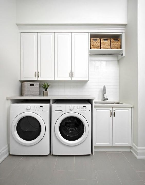 White modern laundry room features raised panel cabinets over an enclosed washer and dryer next to a sink.