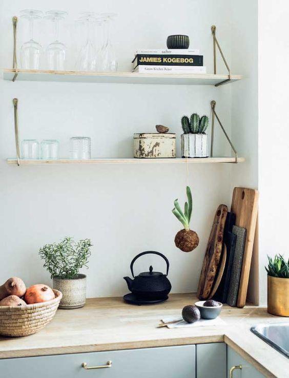 light blue cabinets, wooden shelves, wooden worktop, chopping boards, cast iron kettle, tonal kitchen