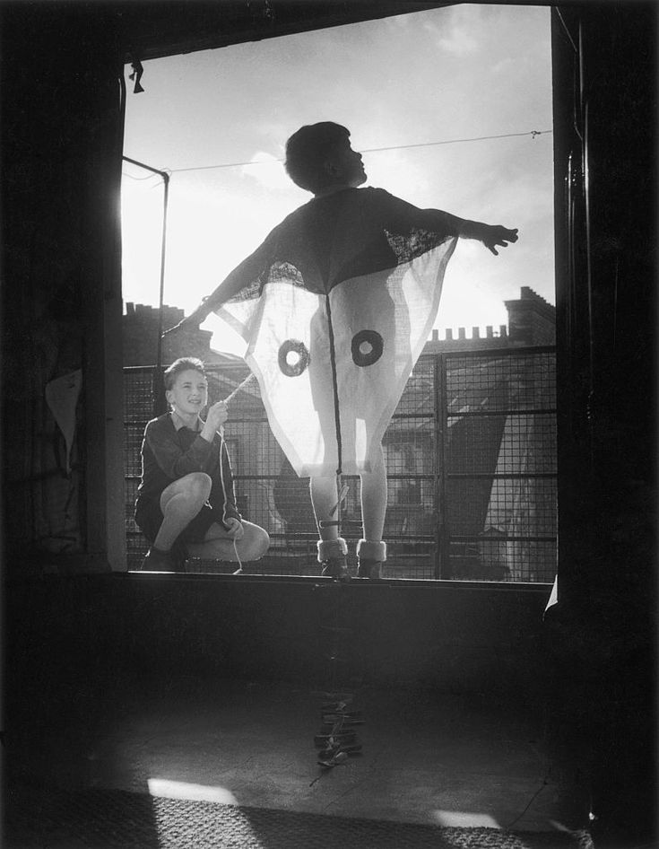 let's go fly a kitechildren playing on a window, pretending to be a kite, unplaced, undated. © willy ronis.