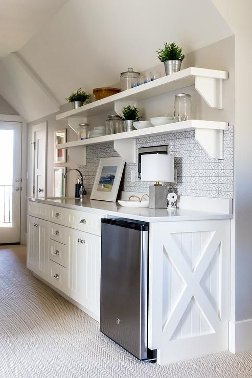 Under a sloped ceiling, a white and gray butler's pantry features white beadboard cabinets accented with polished nickel cup pulls and an x-trim and is fitted with a stainless steel mini fridge positioned under a white quartz countertop.