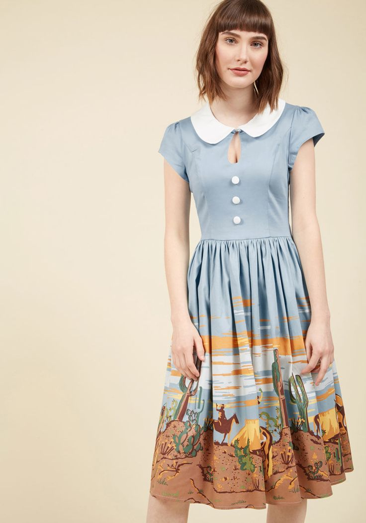 <p>You may search long and hard for frocks that fit your aesthetic perfectly, but as soon as they hit your frame, the result is effortless! This light blue midi's white Peter Pan collar, decorative bodice buttons, and puffed cap sleeves are no exception. As for its gathered skirt, flaunting a desert-toned reel of retro cowgirls? The compliments it earns is where the real payoff happens!</p>